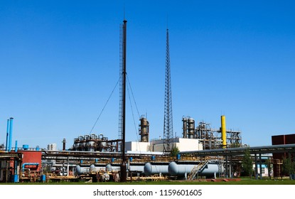 A large concrete technological industrial installation at a chemical petrochemical refinery with capacitive pipes by pumps compressors heat exchangers by pipelines and buildings.