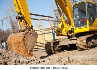 A large construction excavator of yellow color on the construction site for quarrying