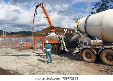 Large construction receiving concrete for foundation through a concrete mixer