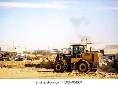 Large construction site in the city. Construction equipment, machinery, excavators, concrete mixers, cranes and bulldozers operate over a large working area. Kazakhstan, Turkestan - March 14, 2021