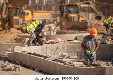 Large construction site in the city. The construction team works over a large working area. Craftsmen go about their business in the open air. Kazakhstan, Turkestan, March 14, 2021