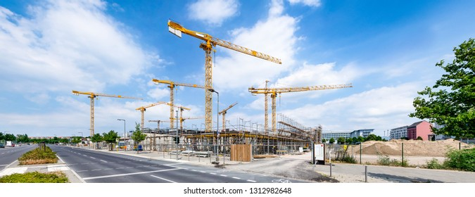 Large construction site with construction cranes as panorama background