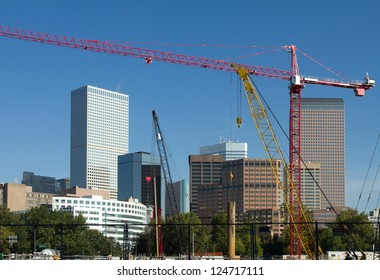 Large construction site in foreground, with the skyscrapers and building of Denver, Colorado in the background on a clear day.