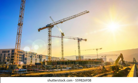 Large construction site including several cranes working on a building complex, with clear blue sky and the sun