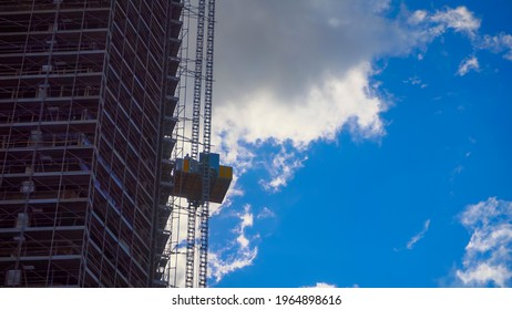 Large construction site with loaded elevators. Tower construction cranes working on a construction site lift a load onto a high-rise building. Summer blue sky. unset and silhouette crane, sunset
