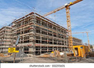 Large construction site with scaffolding building, yellow tower crane and clear blue sky.