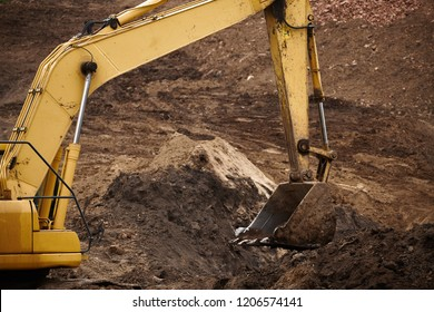 A large construction yellow excavator of yellow color on the construction site in a quarry for quarrying. excavator at sandpit during earthmoving works. Machines of construction site.