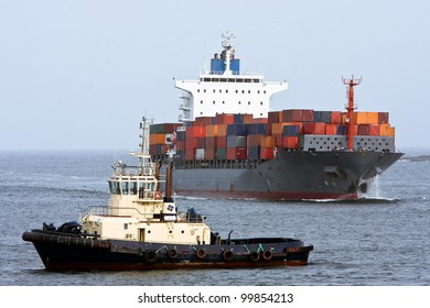 Large container cargo ship and support tug boat, at sea.