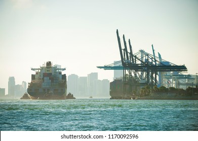 Large container ship being brought into port by tug boats with skyscraper city skyline backdrop