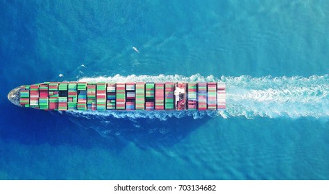 a Large container ship is leaving the port full loaded with containers and cargo - aerial - top down view