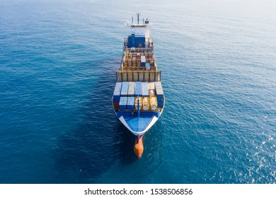 Large Container ship loaded with various colours and brands of shipping containers at sea, Aerial image.