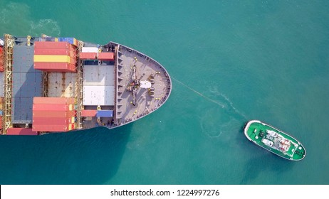 Large container ship pulled into port by a tugboat - Top down aerial image