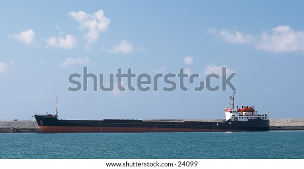 A large container ship tied up at a port in the Mediterranean Sea.