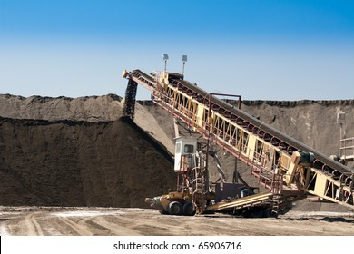 a large conveyor belt carrying golden ore and emptying onto a huge pile