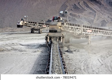 a large conveyor belt carrying golden ore