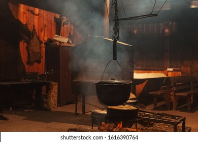 Large cooking pots are prepared using firewood.Metal boilers over a fire in a house with smoke.