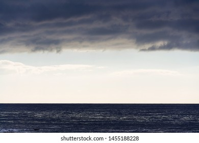 Large copy space for text on sky stripe between sea and clouds, sunrise on summer day