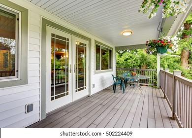 Large covered porch with railings ,outdoor seats, flower pots and turned on lights on the ceiling. Northwest, USA
