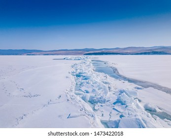 A large crack with bare ice and hummocks passes over the snow-covered surface of Lake Baikal in early spring. View from above. Siberia, Russia