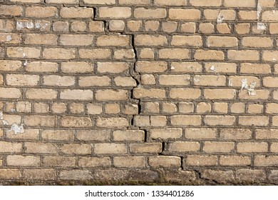 A large crack in the old stone wall. Background of a stone brick wall of a building with a deep through dangerous crack. Ruined wall