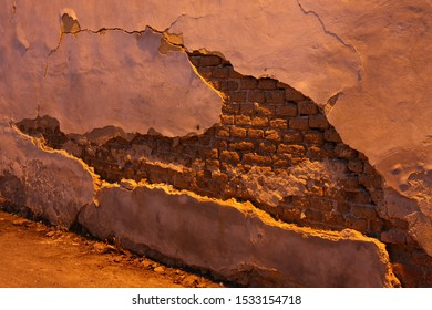 Large crack in a streetside wall with detaching layer of thick plaster. An underlying wall of red bricks is visible below. Lit by yellow to orange light of street lamps at night.