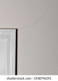 A large crack in the wall extends from the white frame of a doorway.