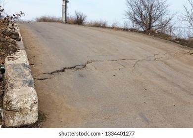 Large cracks, chips, plates. Broken asphalt shifted landslide after an earthquake. Dangerous deep cracks on road. Road closed. Grid of cracks on destroyed asphalt of abandoned road after earthquake