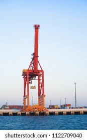 Large crane and cargo port by the sea