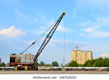Large crawler crane or dragline excavator with a heavy metal wrecking ball on a steel cable. Wrecking balls at construction sites. Dismantling and demolition of buildings and structures - Image