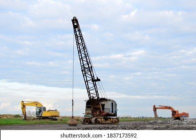 Large crawler crane or dragline excavator with a heavy metal wrecking ball on a steel cable. Wrecking balls at construction sites. Dismantling and demolition of buildings and structures. Out of focus