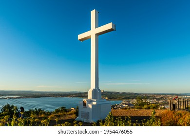 The large cross at the top of Mont Saint Clair in Sète, at sunset, overlooking the Thau lagoon and its oyster tables, in Hérault, Occitanie, France