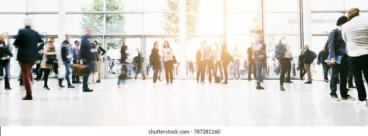 large crowd of anonymous blurred people at a trade show hall