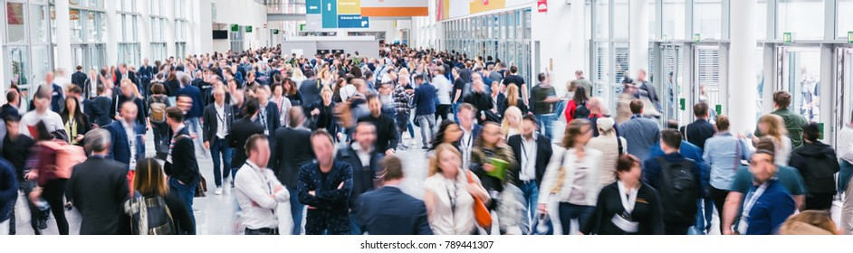large crowd of anonymous blurred people at a trade show