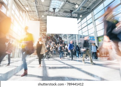 large crowd of anonymous blurred people walking at a trade show
