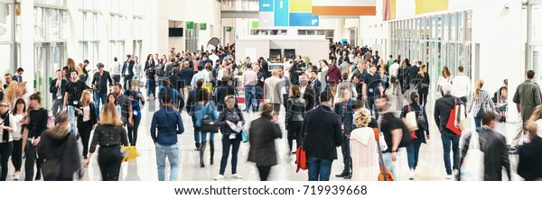large crowd of anonymous blurred people at a trade fair