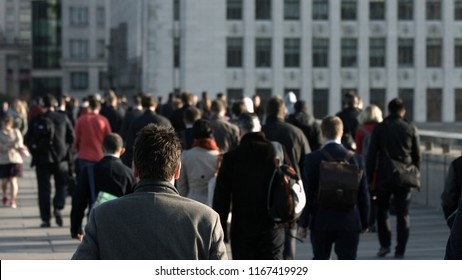 Large crowd of unidentifiable commuters and pedestrians walk across London Bridge to the City of London. In the background is a plain grey building. City workers. Formal clothes. Framed for graphics.