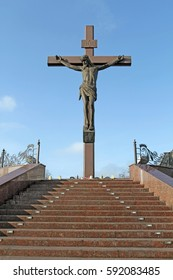 A large crucifix with Jesus Christ under the open sky view directly.
