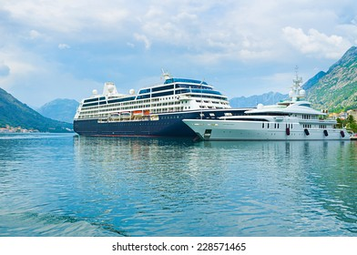 The large cruise liner and white yacht in port of Kotor, Montenegro.