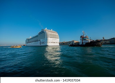 A large cruise ship, MSC Musica, Panama,  being towed in Grand Canal to Venice Port. The large vessels bring many tourists to Venice continuously, Venice, Italy, Sep, 9 , 2012.