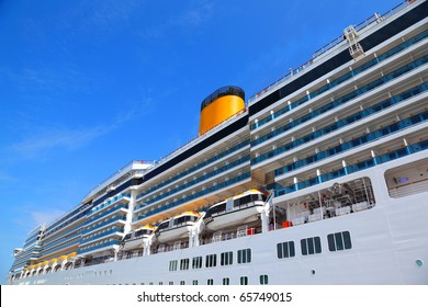 Large cruise ship with yellow funnel and blue balcony rise to blue sky