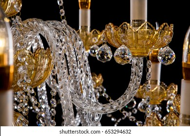 Large crystal close-up chandelier with candles isolated on black background.