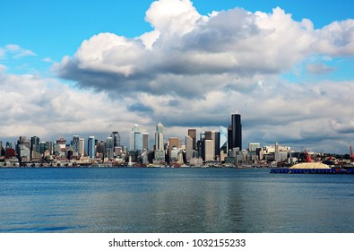 Large cumulus clouds dwarf skyscrapers below with blue water in foreground and barge piled with sawdust