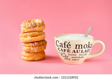 a large Cup of cappuccino coffee and donuts, Breakfast concept, on the Cup inscription in French (mocha coffee, coffee with milk). pink background, selective focus, without logos