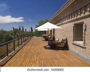 Large deck balcony. Chairs, tables and umbrellas under the sun.
