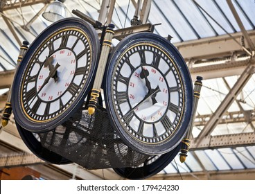 Large decorative clock hanging from a train station roof