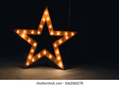 Large decorative retro star with lots of burning lights on grunge concrete background
