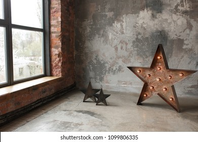 Large decorative retro star with lots of burning lights on grunge concrete background near window frame. Beautiful decor, modern design element. The loft style studio. Free space for text