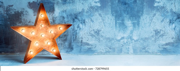 Large decorative retro star with lots of burning lights on grunge concrete background. Beautiful decor, modern design element. The loft style studio. Free space for text