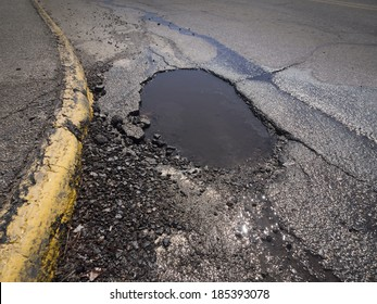 Large deep pothole as an example of poor road maintenance due to cutbacks on the infrastructure budget