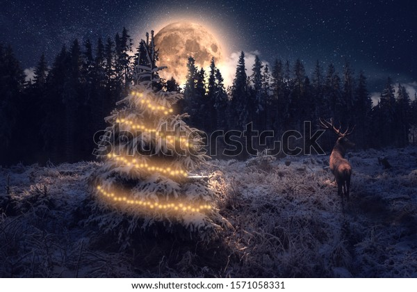 Large deer with moon in a Winter landscape next to a decorated Christmas tree